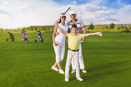 Happy boy golfer plaing golf with parents Stock Photo