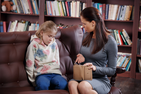 Strict young mother scolding little girl about money Banque d'images