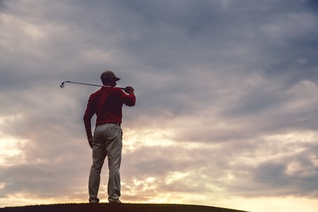 silhouette of man golfer with golf club at sunset. back view Stock Photo