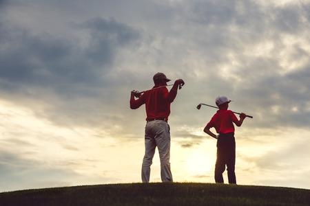 man met zijn zoon golfers staan op de golfbaan bij zonsondergang, achteraanzicht Stockfoto