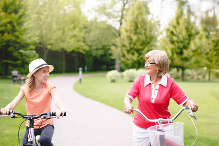 grandaughter: Happy active senior woman riding bike with her grandaughter in park at summer