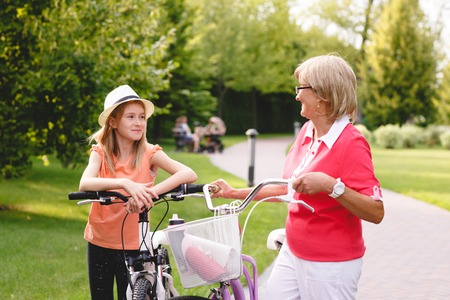 grandaughter: Happy active senior woman relaxing after riding bike with her grandaughter in park at summer