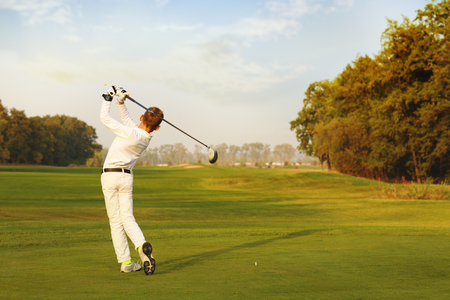 Boy golf player hitting by iron from fairway at autumn evening Banque d'images