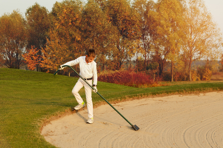 Boy golf player rake the bunker area from footprints at autumn sunset Stock Photo