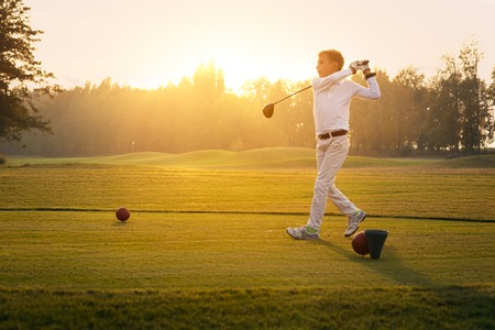 Boy golf player hitting by iron from fairway at sunset Stock Photo