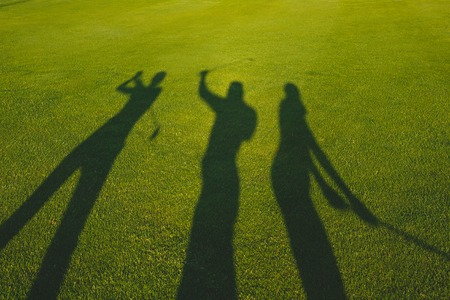 Three golfers with open hands silhouette on grass Stock Photo