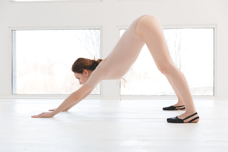 Full length side view portrait of beautiful young woman working out, doing stretching or pilates exercise on wooden floor Stock Photo