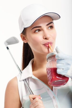 Pretty girl golfer with jar of detox juice in studio