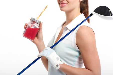 Pretty girl golfer with jar of detox juice in studio