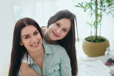 Beautiful mother and her cute daughter smiling and posing at home.