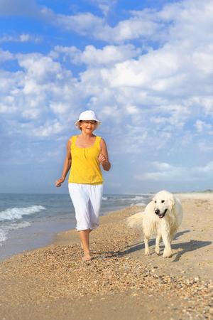 Bejaarde die met haar golderretriever loopt