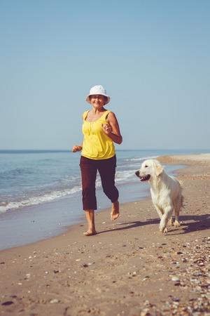 Elderly woman running with her golder retriever