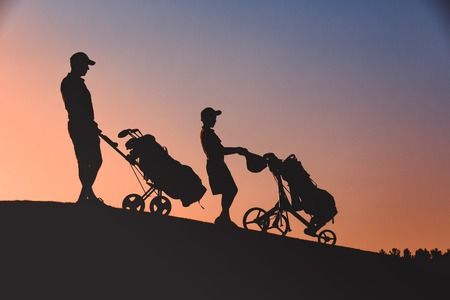 man with his son golfers silhouette
