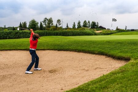 Boy golf player chipping from sand bunker onto green Stock Photo
