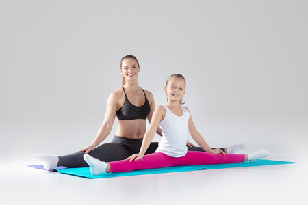 Beautiful woman and her little daughter are doing exercises on mats
