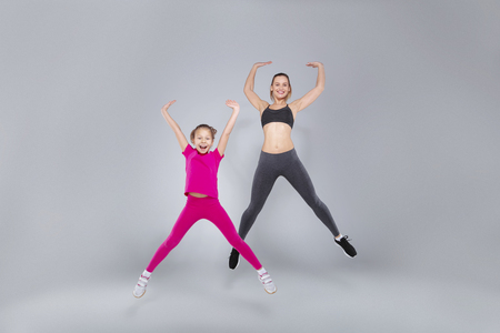 Beautiful woman and her daughter are jumping at the gym