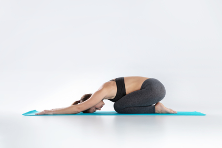 Beautiful woman doing sport exercises on mat