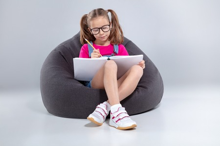 Young girl in glasses doing homework on a gray bean bag