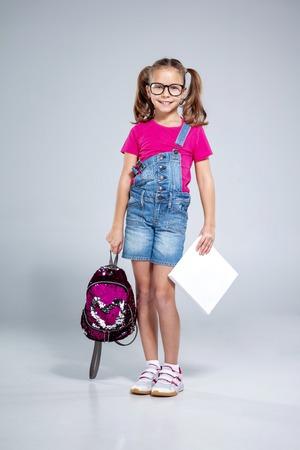 Colegiala en gafas con mochila y libro de texto sobre fondo gris Foto de archivo