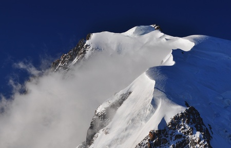 massif: Mont Blanc du Tacul is a mountain in the Mont Blanc massif of the French Alps situated midway between the Aiguille du Midi and Mont Blanc Stock Photo
