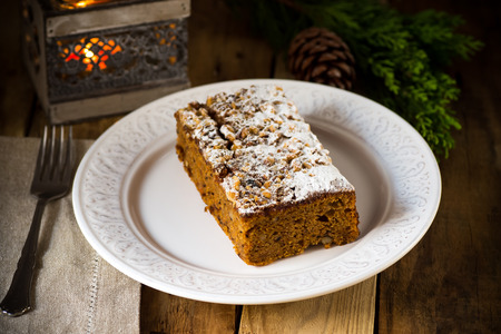 Kerst carrot cake op een plaat met een brandende kaars, dennenappels en jeneverbessen takje op een verouderde houten tafel