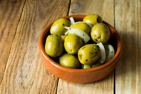Jumbo gordal green olives with herbs and onions on distressed wood background