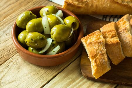 Jumbo gordal green olives with herbs and onions With rustic baguette on wood background