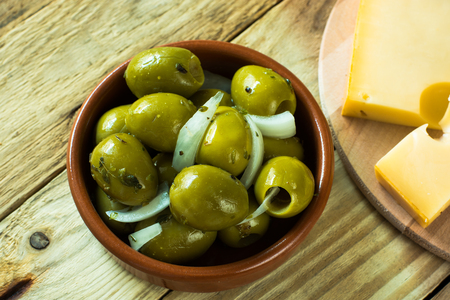 Jumbo gordal green olives with herbs, cheese on wood background top view Stock Photo