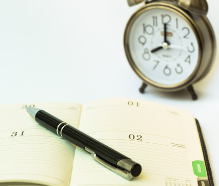 hectic life: Day timer organizer with a pen and a mechanical alarm clock, time management and activity planning concept, organization busy schedule, close up