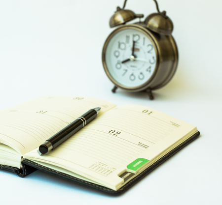 hectic life: Day timer organizer with a pen and a mechanical alarm clock, time management and activity planning concept, busy schedule organization, selective focus Stock Photo
