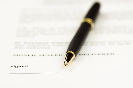 signing papers: Contract signing close up focus on the tip of a ball point pen laying on the document, business and legal concept