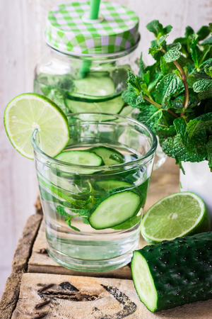 Infused detox water with cucumber, mint and lime in glass and jar mug, with ingredients