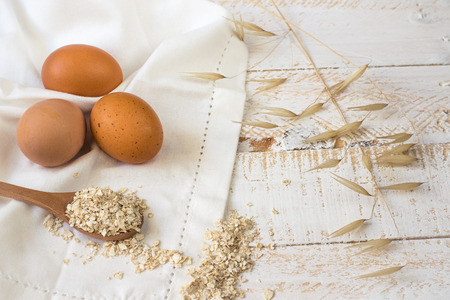 mindful: Brown eggs, dry oatmeal flakes on wooden spoon scattered over white linen cloth, wood background, healthy ingredients, mindful eating, beauty, skin care concept