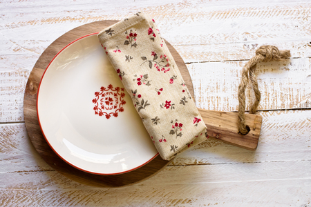 kinfolk: Off-white plate with red empty board on round cutting board, floral linen napkin, white plank wood background, Provence style, rural kitchen interior, minimalistic, kinfolk, lay flat Stock Photo