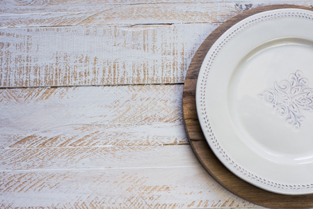 kinfolk: Vintage White empty plate on round cutting board, white plank wood background, Provence style, kitchen interior, minimalistic, kinfolk, lay flat, selective focus