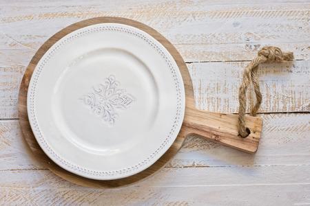 kinfolk: Vintage White empty plate on round cutting board, white plank wood background, Provence style, kitchen interior, minimalistic, kinfolk, lay flat