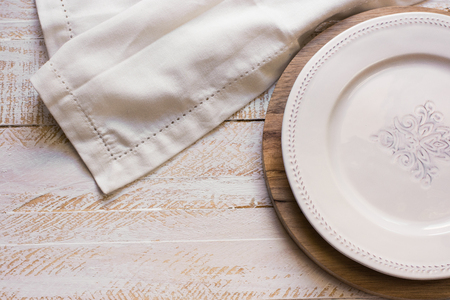 kinfolk: Vintage White empty plate on round cutting board, white linen cloth over wood background, Provence style, kitchen interior, minimalistic, kinfolk, selective focus