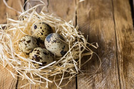 kinfolk: Quail eggs in a straw nest on barn wood, farming, Easter concept, organic healthy food