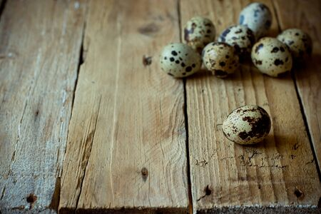 kinfolk: Scattered quail eggs on aged wood plank background, vintage style rustic, Easter