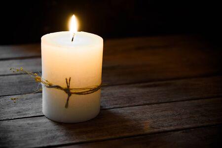 kinfolk: Large white candle burning on aged wood background, tranquility concept, contemplation, meditation