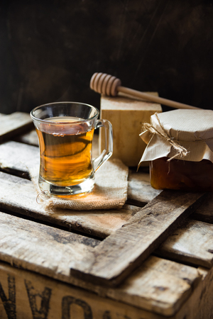 kinfolk: Glass cup with hot tea with honey or jam jar of, wood spoon, on vintage box, black wall background, vintage interior rustic, cozy atmosphere Stock Photo