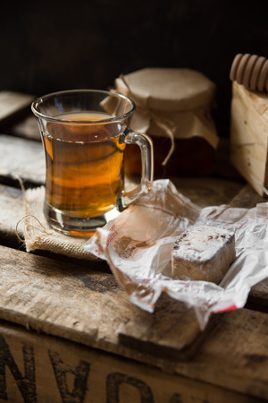 kinfolk: Glass cup with hot tea with honey or jam jar of, wood spoon, Spanish polvoron on vintage cookie box, black wall background, inside rustic countryside, cozy atmosphere Stock Photo
