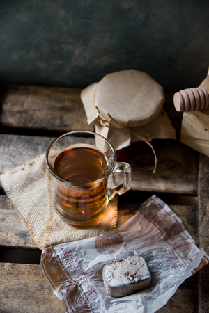 kinfolk: Glass cup with hot tea with honey or jam jar of, wood spoon, Spanish polvoron on vintage cookie box, gray wall background, vintage interior rustic, cozy atmosphere, top angle view