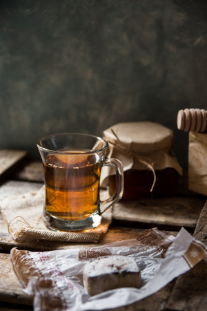 Glass cup with hot tea with honey or jam jar of, wood spoon, Spanish polvoron on vintage cookie box, gray wall background, vintage interior rustic, cozy atmosphere Stock Photo