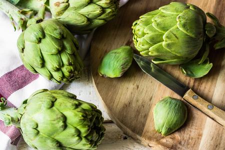 Peeling fresh ripe artichokes, preparing for cooking, wood cutting board, knife, kitchen linen towel, top view