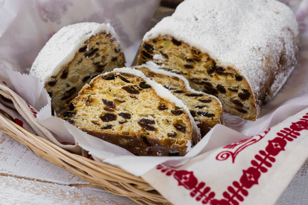 German Christmas stollen cut into slices, powdered, in wicker basket, kitchen towel with ornament, top view