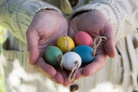 Young woman holding in hands Easter eggs on twine, kinfolk