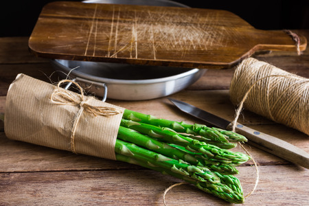 Bundle of fresh organic asparagus wrapped in craft paper on kitchen table, cutting board bowl knife, daylight, cozy atmosphere Stock Photo