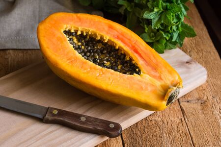 Ripe papaya cut in half on wood cutting board, bunch of fresh mint on rustic kitchen table by window, kinfolk, authentic style Archivio Fotografico