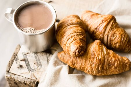 Freshly baked croissants on linen cloth mug with hot cocoa on vintage wood box. Cozy atmosphere breakfast